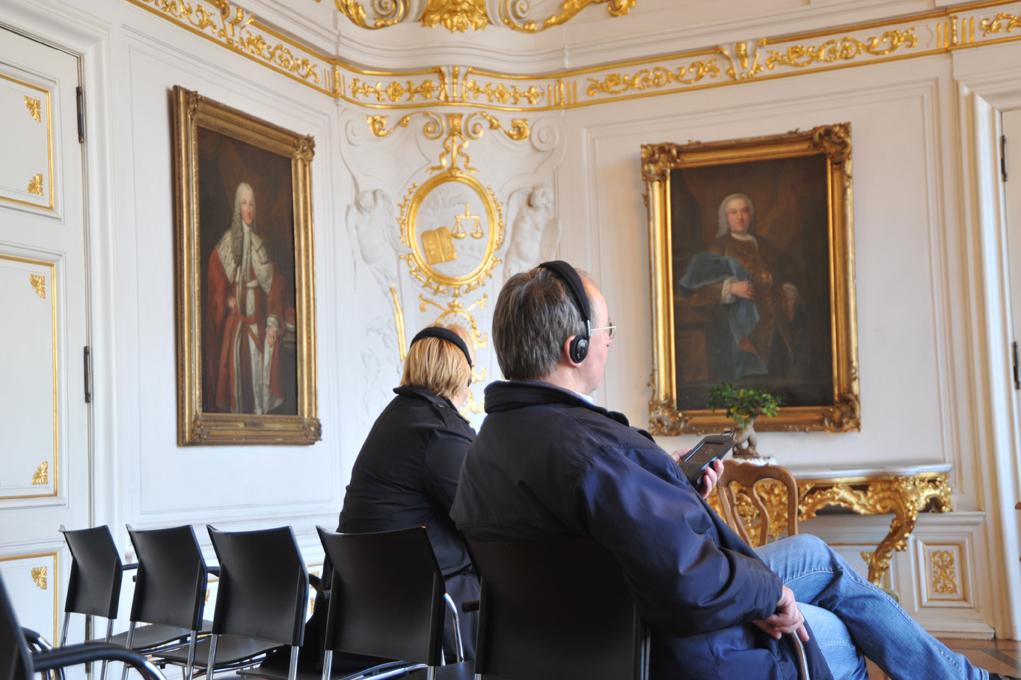 Besucher lauschen dem Aixplorer. Auf dem Gemälde links ist der Earl of Sandwich dargestellt, auf dem Bild rechts Gerard Arnold Hasselaer (1698-1766), Gesandter der Republik der Niederlande. Beide Gemälde stammen von Jean Fournier.
